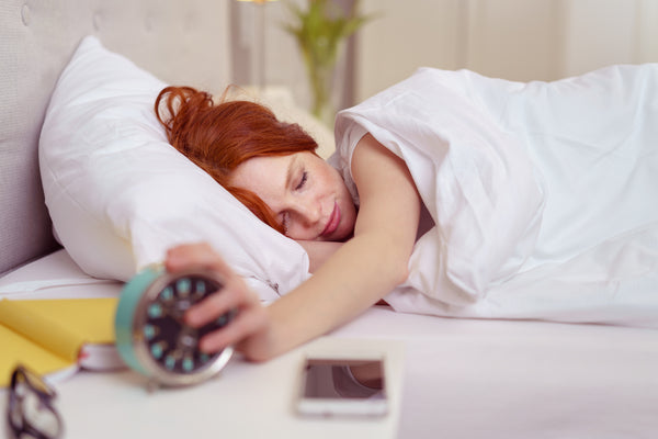 woman stopping alarm clock while ion bed