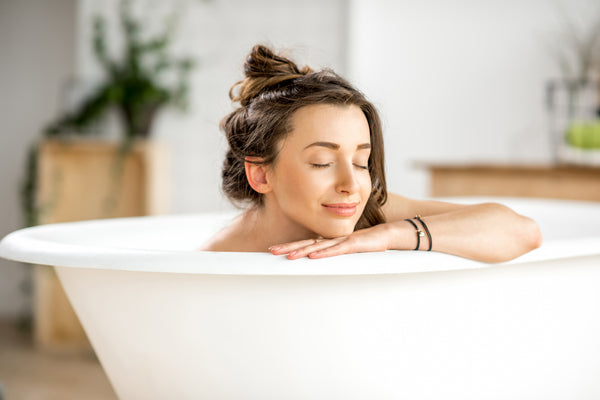 Young woman relaxing lying in the bathtub