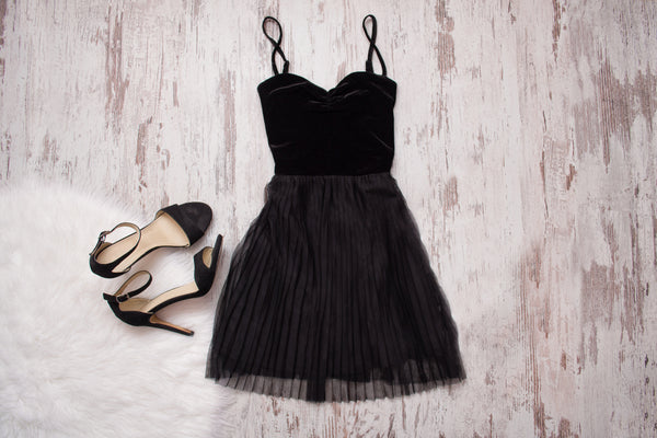 Little black dress and black shoes. Wooden background