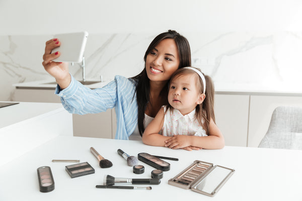 Happy young woman with little daughter make selfie