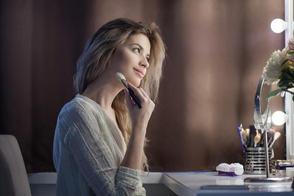 relaxed woman doing makeup in front of mirror