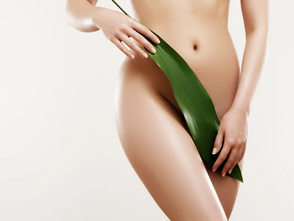 woman holding aloe leaf across her body