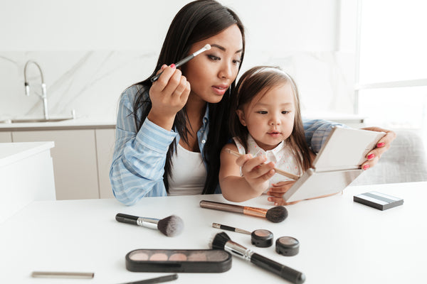 Young pretty asian mother doing make up with daughter