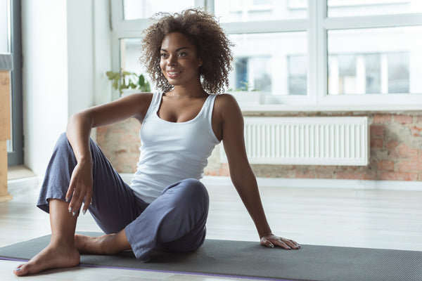 Beaming girl sitting on exercise mat in apartment
