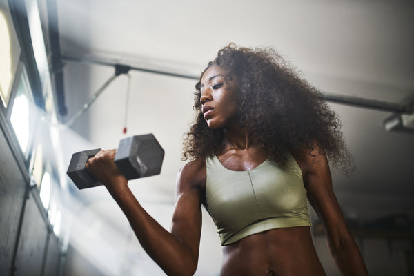 fit african american woman working out by lifting weights