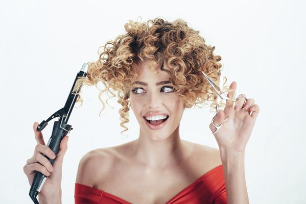 woman with curlers and scissors deciding on hair style