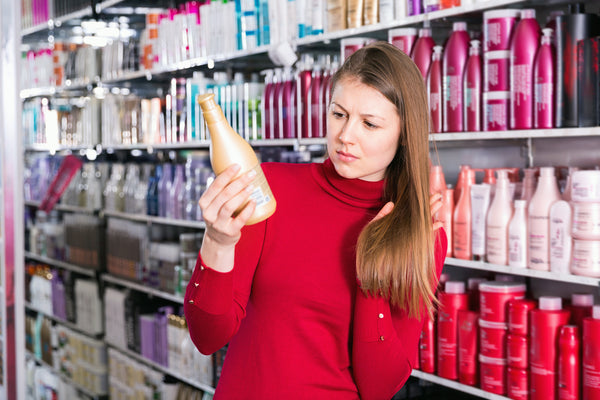 Young woman deciding on a new conditioner for hair