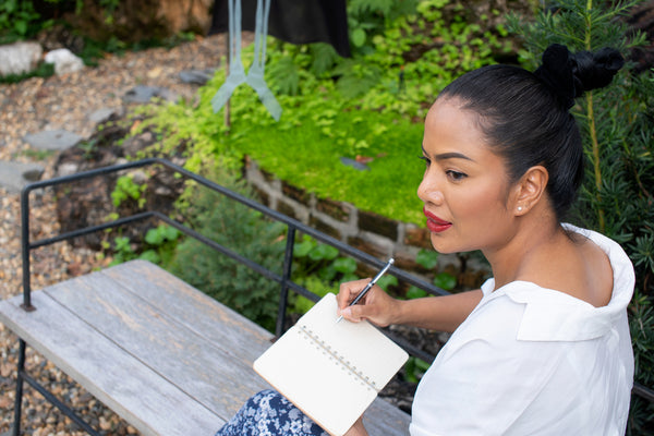 beautiful woman writing in a book outside