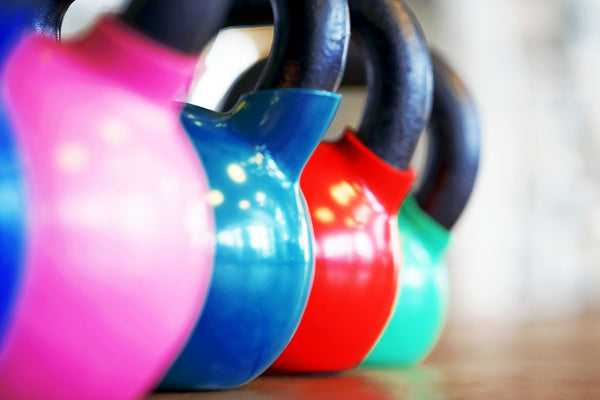 Close-up colorful kettlebells in a row on the wooden floor