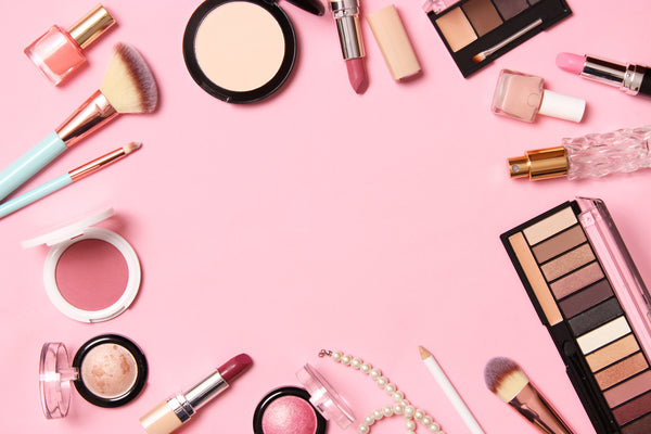 professional makeup tools and makeup products on pink background