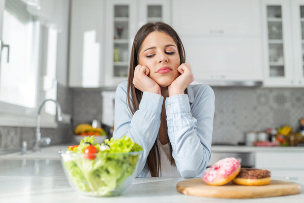 Teenage girl chooses between donuts and vegetable salad