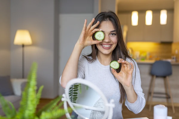 Girl holding cucumbers to cleanse face