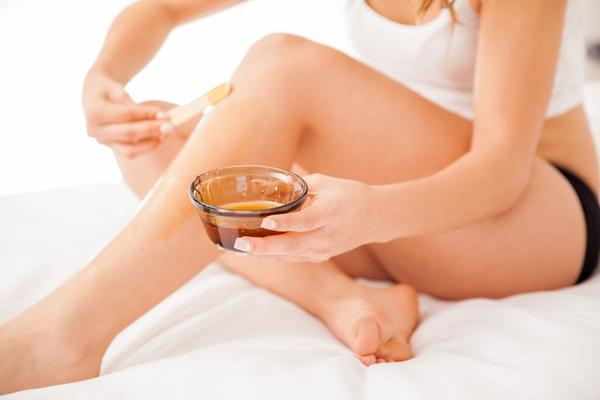 beautiful woman applying wax to legs