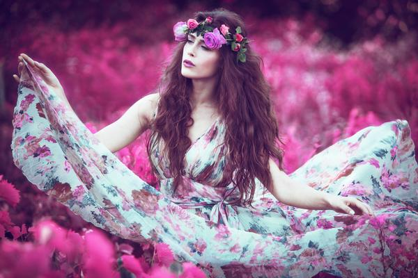 beautiful model in floral dress surrounded by flowers