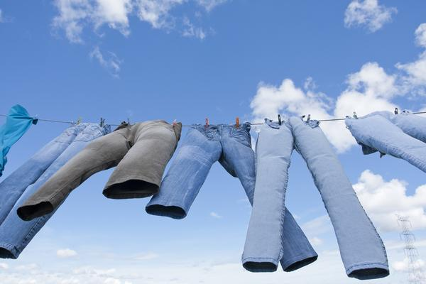 jeans hanging on washing line in clear blue sky