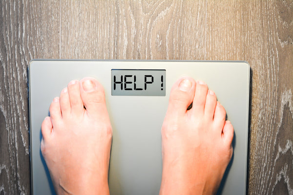 "Lose weight concept with person on a scale measuring ""help"""