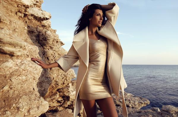 model wearing gold bandage bodycon dress with a coat