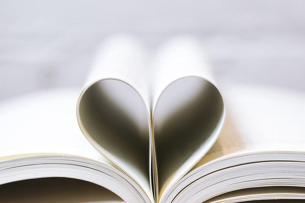 An open book with pages curled into one another to form the shape of a heart.