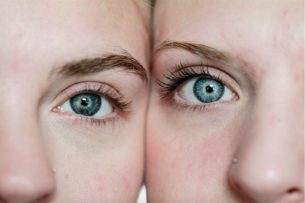 A close up macro shot of two girls with blue eyes accepting close boundaries