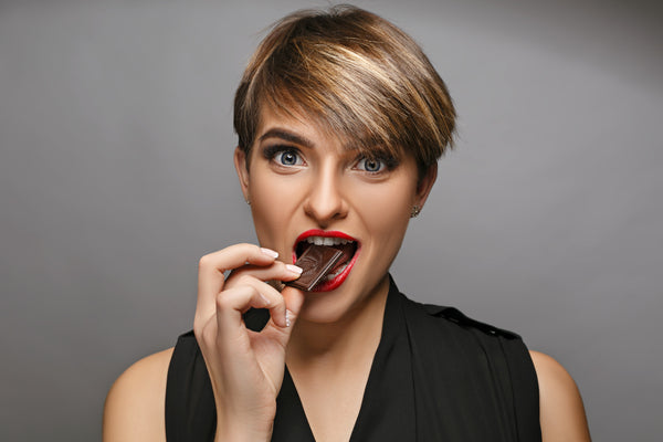 girl eating a piece of  chocolate