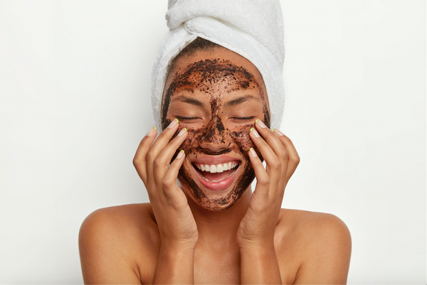 Portrait of cheerful smiling dark skinned woman applies natural coffee mask