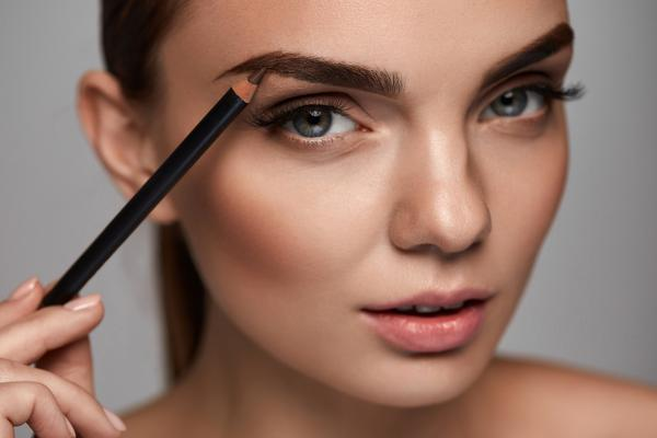 woman with eyebrow pencil shaping eyebrow