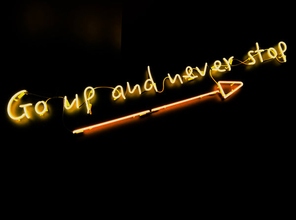 """The words """"go up and never stop"""" in neon"""