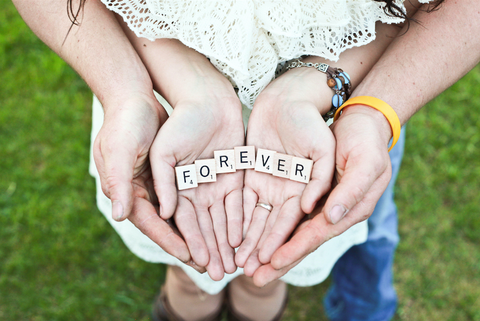 Couple holding the word forever in their hands
