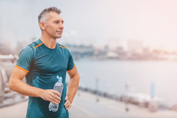Portrait of healthy athletic middle aged man with fit body holding bottle of refreshing water, resting after workout