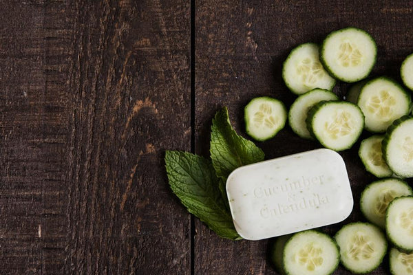 Handmade soap on a wooden background accompanied with it's ingredients, cucumber and calendula
