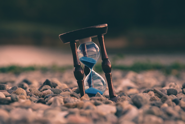 Brown and blue hourglass resting on stones