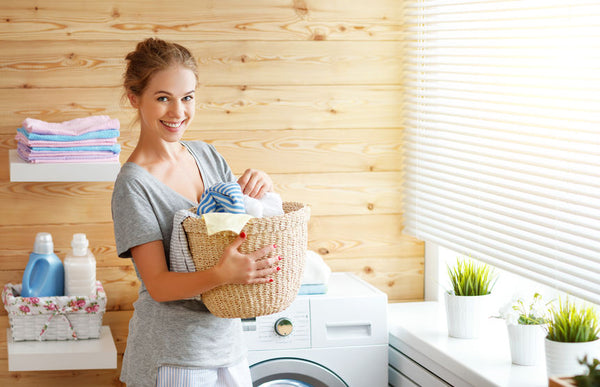 Girl in laundry room holding clothes for washing and ironing