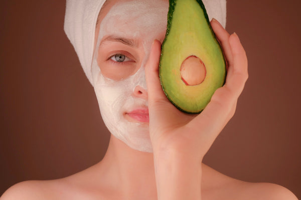 Girl in beauty face mask holding avocado