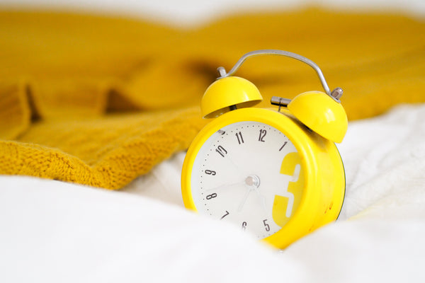 Yellow alarm clock on bed