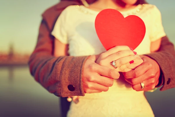 Loving couple holding heart in hands
