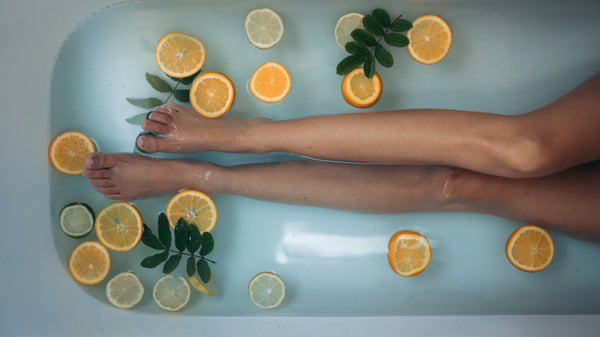 Girl in bath surrounded by oranges