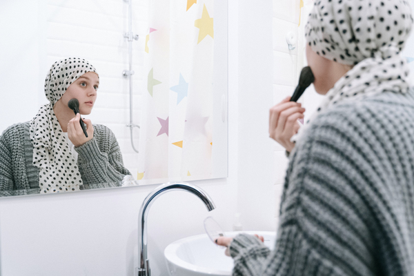 Woman with full headscarf applying makeup