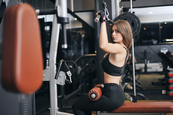Girl at gym with weight lifting gloves