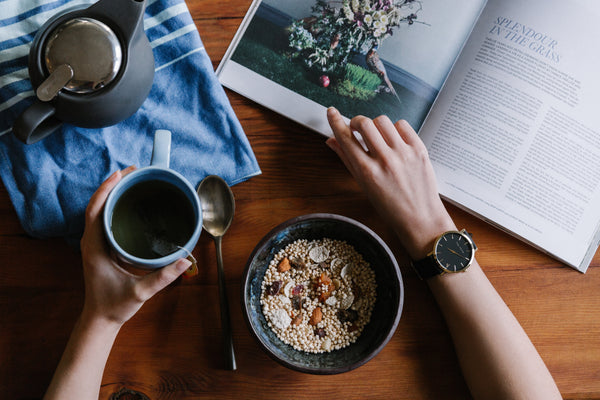 Woman eating breakfast and reading a book