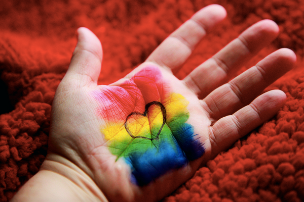 Gay and lesbian flag drawn on palm with heart