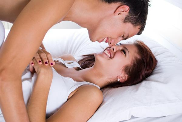 Young couple smiling at each other on bed