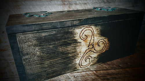Front view of rustic alter box with triskelion wood burn.