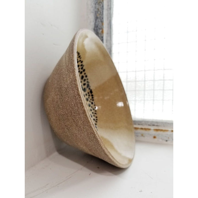 tan speckled bowl with black dot interior detail
