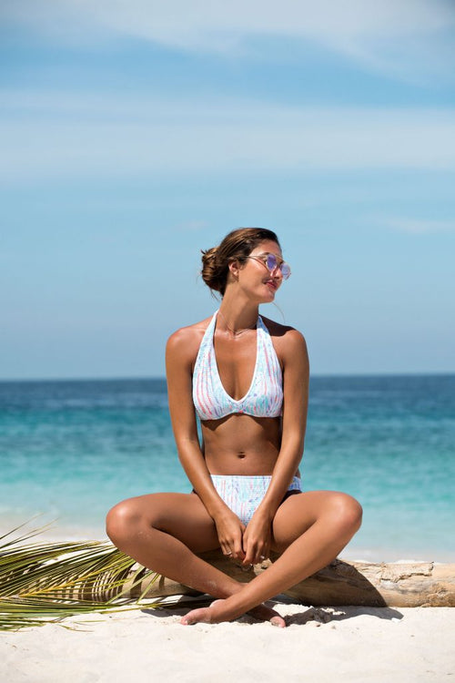 Sunseeker Swimwear model seated on a tree log and wearing a halter bikini top with high waisted bikini bottoms