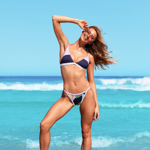 Sunseeker Swimwear model smiling by the shore wearing an Illustrated Fantasy two piece swimsuit