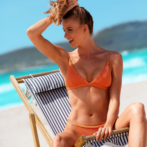 Sunseeker Swimwear model holding her hair up and wearing an orange two piece bikini