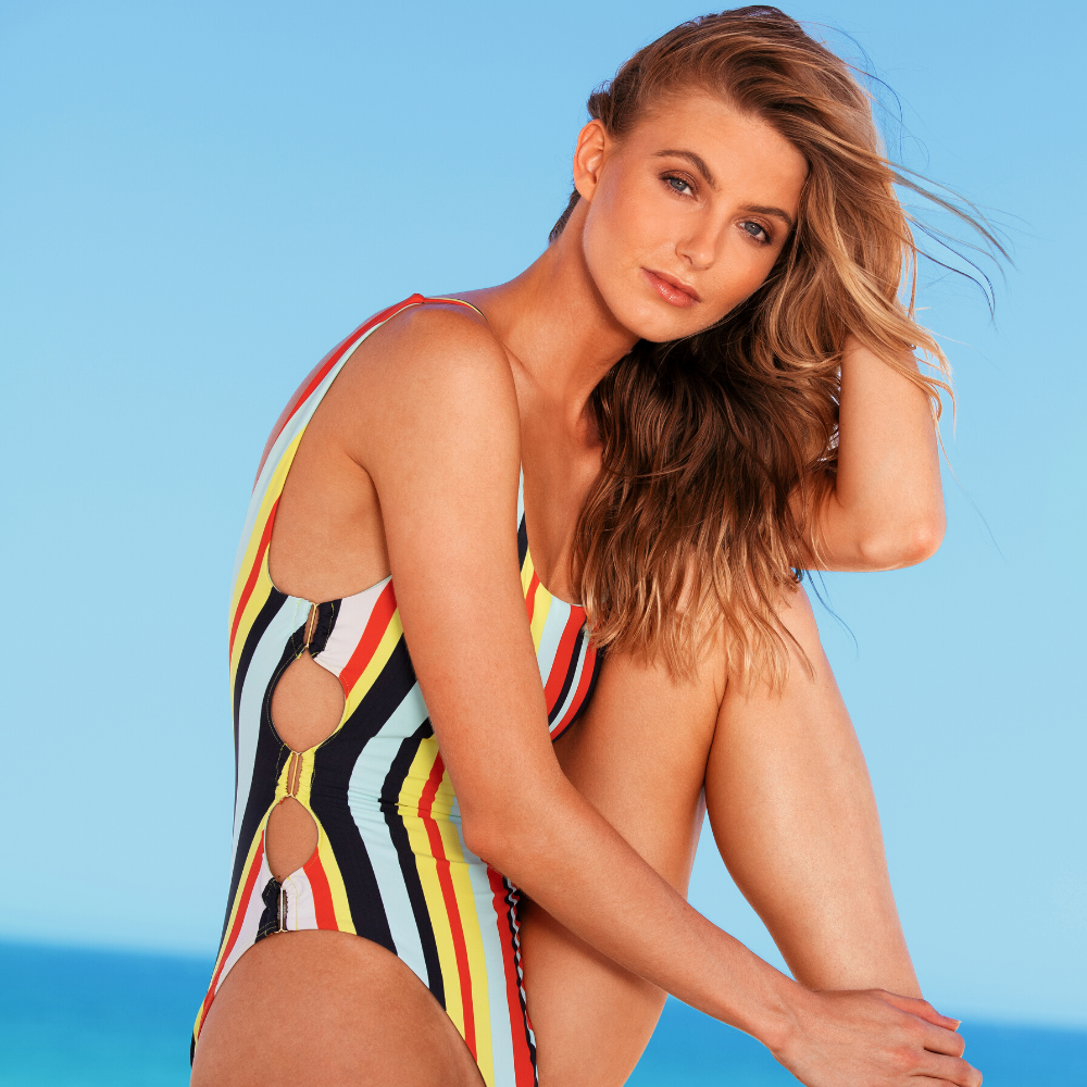 Sunseeker Swiwmwear model seated and wearing a one piece striped swimsuit with a side cut out