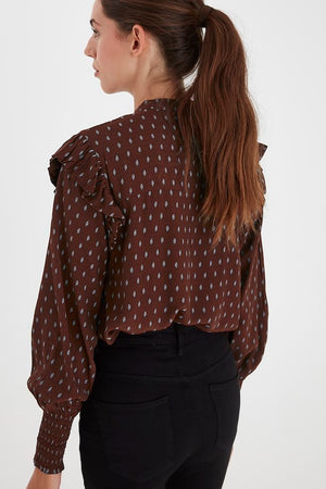 Back view of model wearing ICHI Carina long sleeve printed blouse. Cappuccino brown with light blue print. Frilled detail at shoulders, shirred cuffs.