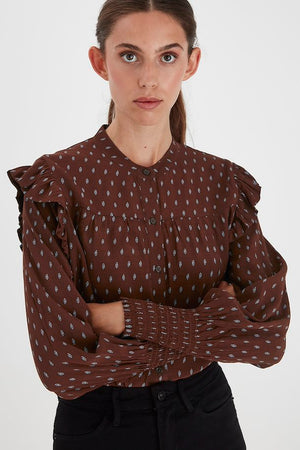 Front view of model wearing ICHI Carina long sleeve printed blouse. Cappuccino brown with light blue print. Frilled detail at shoulders, shirred cuffs.
