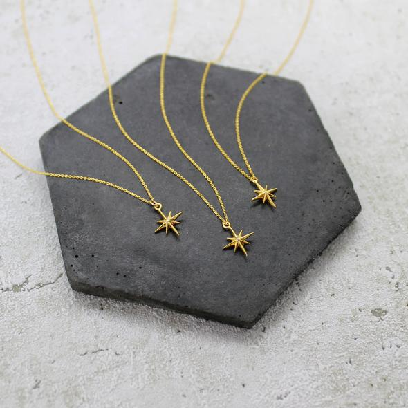 Collection of Mara Studio gold star charm hanging on gold plated necklace. Mint Tea Boutique